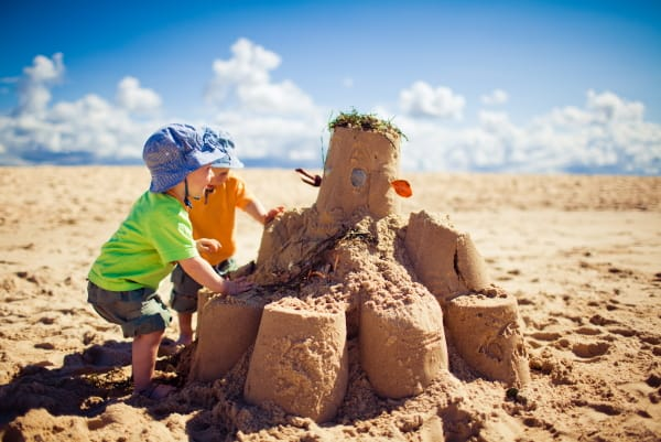 toddlers at the beach playing in the sand