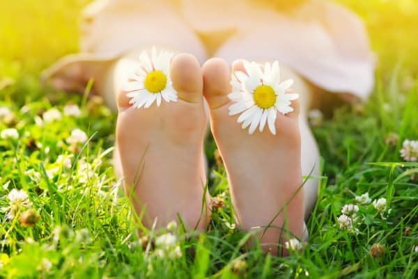 young girls feet with flowers, laying in the grass