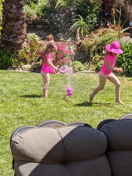 Girls playing in sprinkler