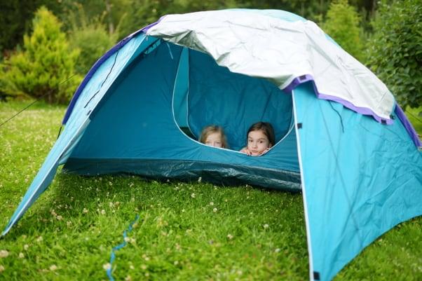 Girls peeking out of tent camping