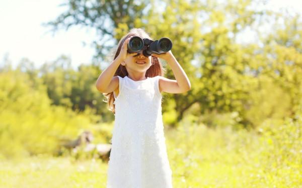 young girl using binoculars