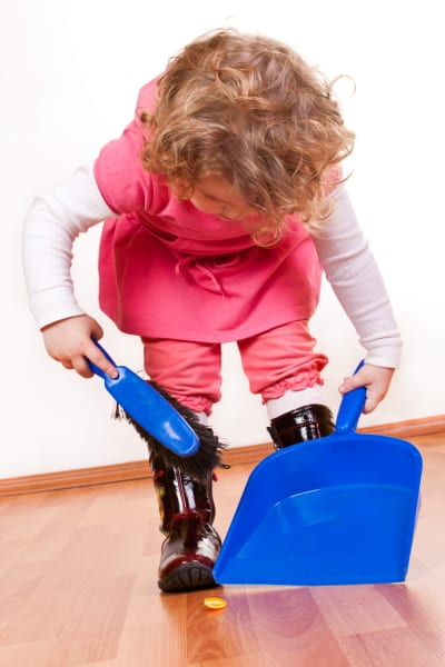 toddler sweeping with dustpan