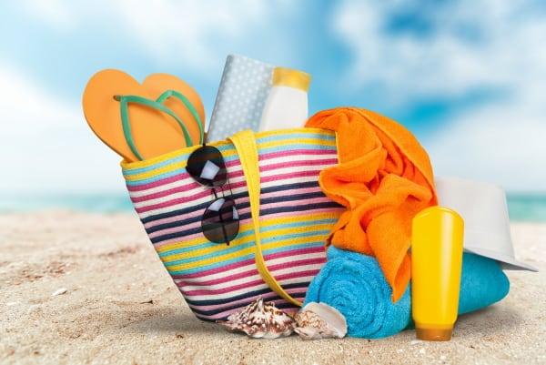beach bag on the sand with beach items