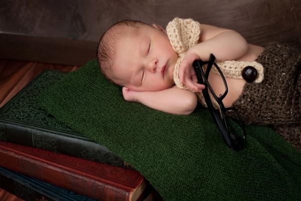 newborn asleep on pile of books