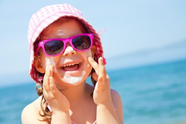 girl at the beach sunscreen on face