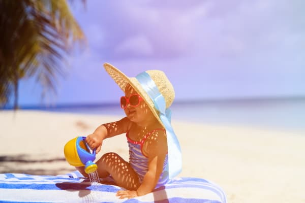 girl on beach with hat, shade, sunscreen