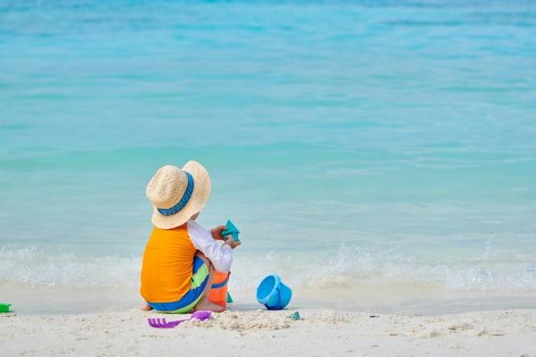child on beach with hat, sunscreen, rashgaurd