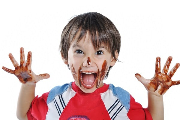 Kid with chocolate on hands and face, snack melted
