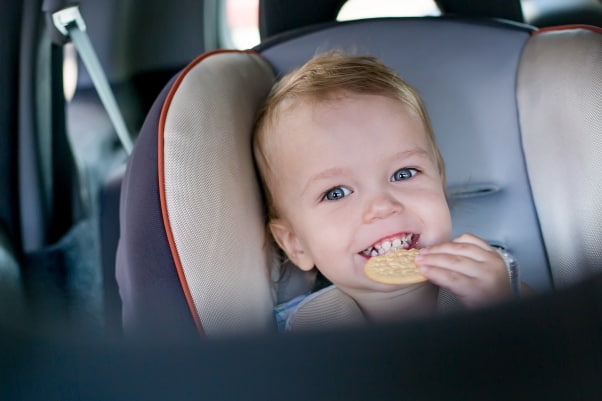 Toddler eating snack in carseat