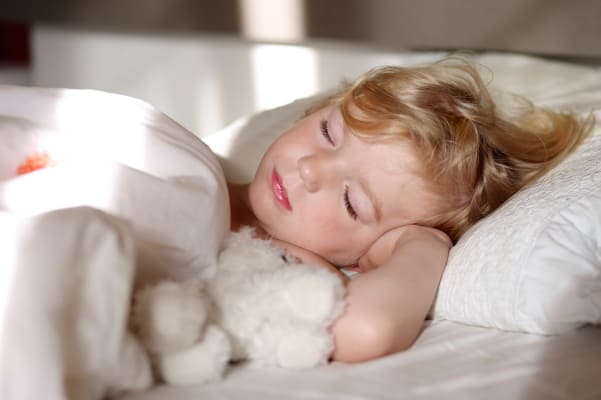 toddler girl sleeping in bed with stuffed toy