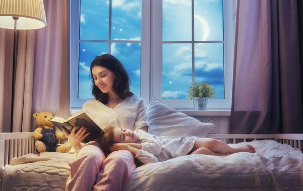 Adult reading to toddler at bedtime