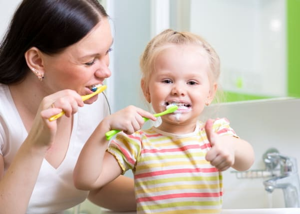 Toddler and mom brushing teeth for bedtime