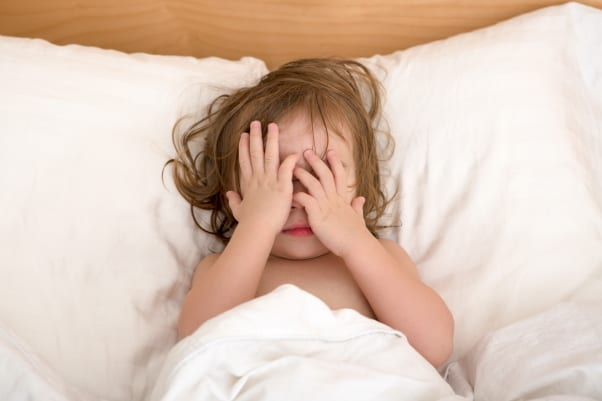Toddler in bed covering her eyes