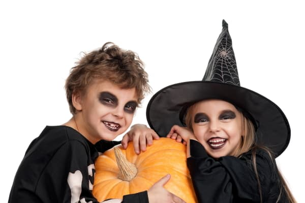 boy and girl in Halloween costumes holding a pumpkin